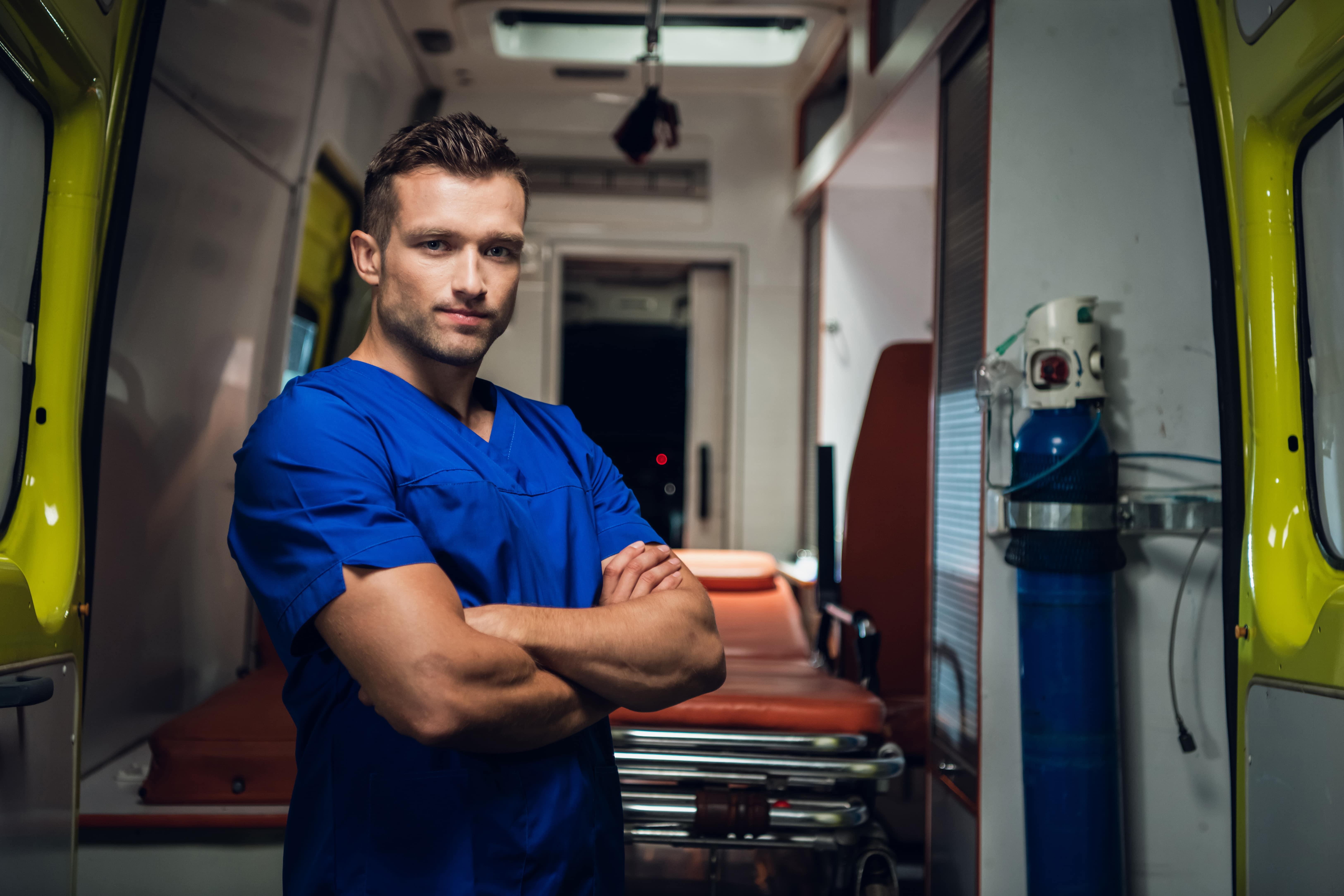young-paramedic-looking-camera-smiling-ambulance-car-background-min